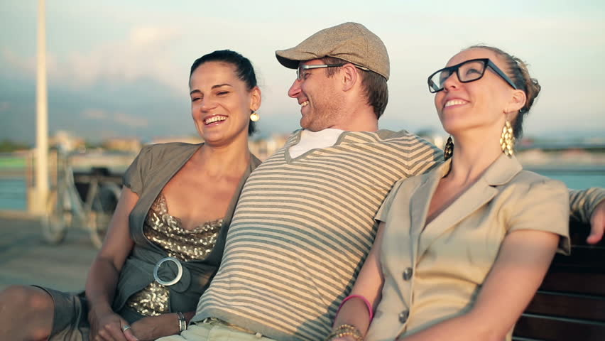 Happy friends sitting on bench and talking, outdoors  | Shutterstock HD Video #3110464