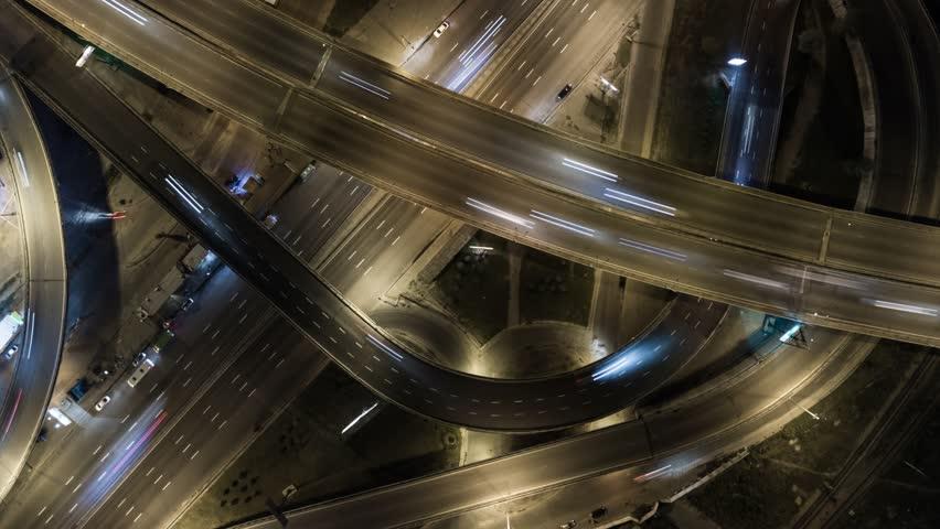 Traffic on freeway interchange. Aerial night view timelapse city traffic.  UHD, 4K