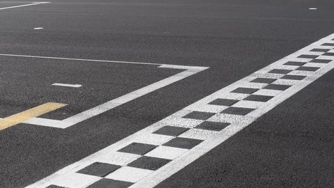 Checkered line and number one sign closeup on racing motorsport track, blurred cars crossing finish line symbol of win, end of the race, first position