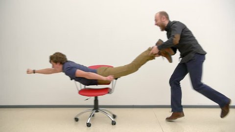 Office chair race. Slow motion. Young guys have fun in office during a break. Games of businessmen from large offices. Men celebrate a successful deal and throwing papers up. Office business party.