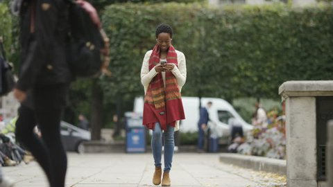 Attractive young female videoing herself on her phone as she walks outdoors in the street