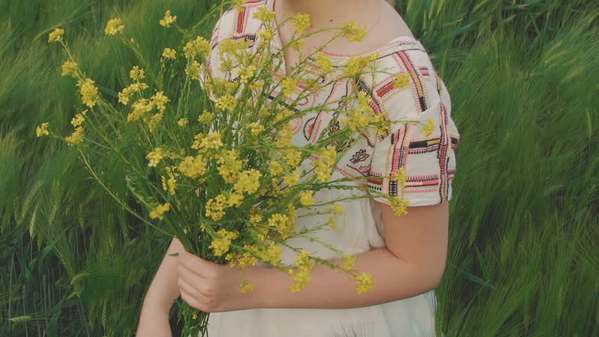 Cute young girl holds the bouquet of rape flowers and sniffs it in the field | Shutterstock HD Video #31126672