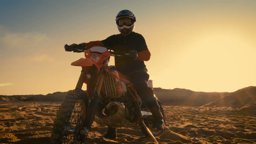 Low Angle Shot of the Professional Motocross Motorcycle Rider Standing on the Path of the Off-Road Track. It's Sunset and Track is Covered with Smoke/ Mist. Shot on RED EPIC-W 8K Helium Cinema Camera.