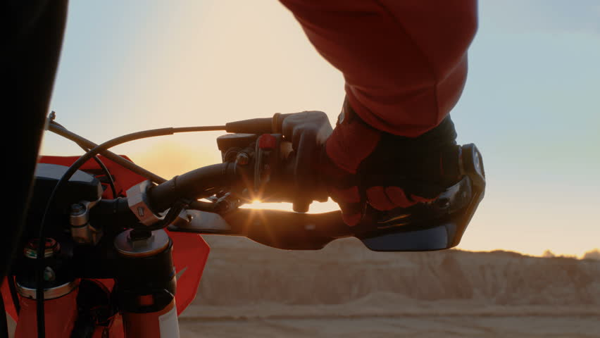 Close-up of the Motorcyclist's Hand Twisting Throttle Handle While Standing on the Scenic Quarry Off-Road Terrain in the Sunset. Shot on RED EPIC-W 8K Helium Cinema Camera.
