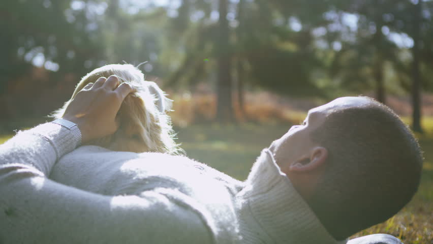 A man affectionately strokes his pet dog as they lay down together outdoors in the early morning sunshine. In slow motion.