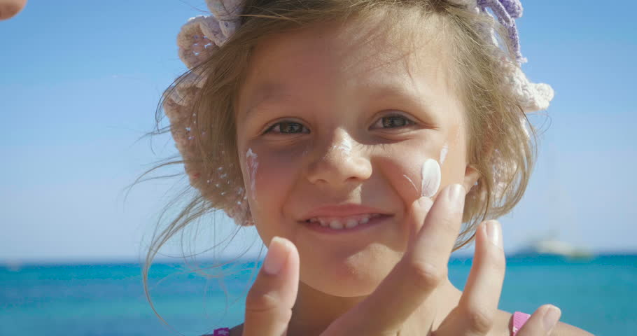 Portrait of beautiful little girl having fun on the sea, cute smiling in panama, sun protection cream, background of sea blue water and rocks. Concept: children, childhood, summer, freedom, kids, baby | Shutterstock HD Video #31132684