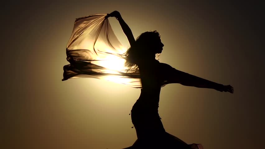 Girl with a veil in her hands dancing belly dance on the beach. Silhouette. Slow motion