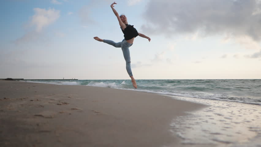 Young woman in casual style - jeans and black top doing ballet at the beach. Attractive ballerina practices in jumping on sandy coastline in autumn. Slow motion.