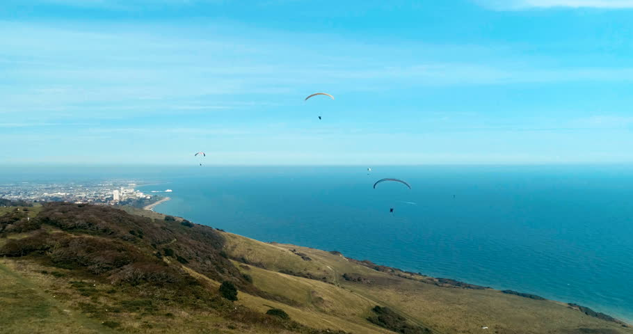 Aerial view of paragliders at Beachy Head, Southern England, with the sea and the town of Eastbourne