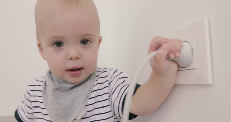 High Quality Curious Little Boy Playing With Electric Plug. Trying To Insert It Into The  Electric Socket