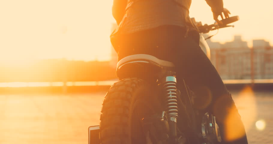 Beautiful Caucasian female biker mounts her custom built cafe racer motorcycle on a rooftop parking lot, beautiful sunset over city in the background. 4K UHD 60 FPS