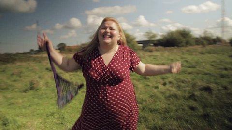 A fat village girl dances on a field. HD