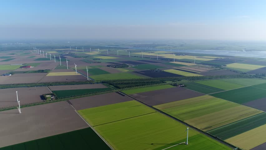 Bird view aerial of polder landscape showing different colors of the farm land and also showing wind turbines providing renewable energy from wind typical dutch flat land far horizon 4k quality