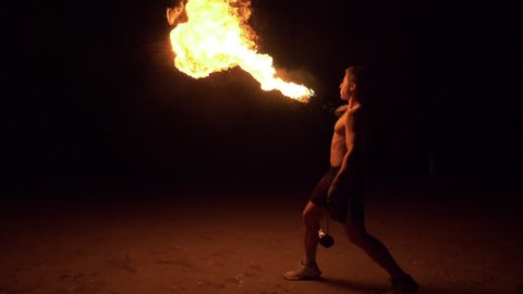 Muscular young man is spraying kerosene on fire torch and erupting flame. Fire show. Slow motion