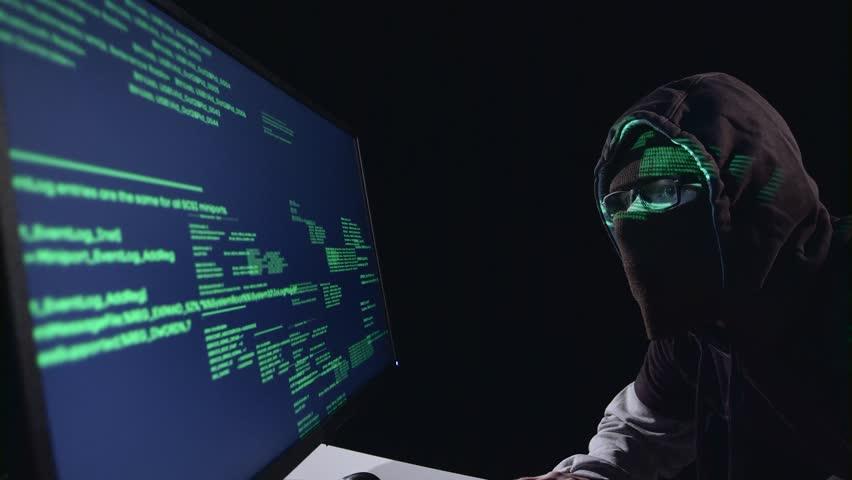 Spy Hacking Computer Sitting In A Dark Room. Black Background   4K Stock  Video Clip