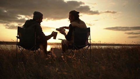 Two men sitting in camping chairs in a field watching sunset pouring tea from thermal mugs.