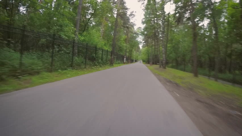 A bike ride along an asphalt road in a park along the fence | Shutterstock HD Video #31236814