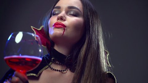 Vampire Halloween Woman drinking red wine. Beauty Sexy Vampire Girl. Vampire makeup Fashion Art design. Attractive model girl wearing Halloween party costume and make up. 4K UHD video 3840x2160