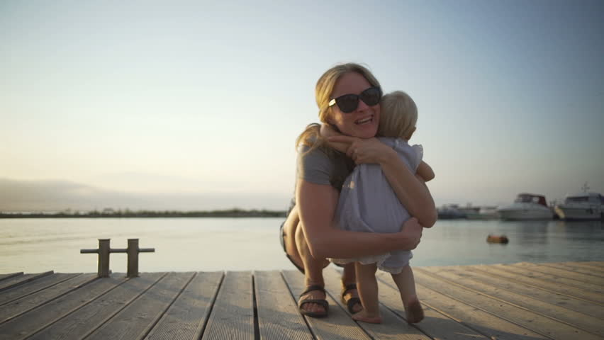 Happy girl playing with baby at sunny pier seaview sunset rapid slow motion