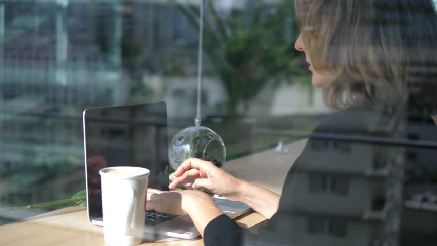Business Woman Working with Laptop Computer Drinking Coffee In Cafe. 4K.