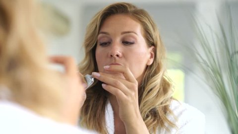 Portrait of attractive blond woman applying anti-aging cream