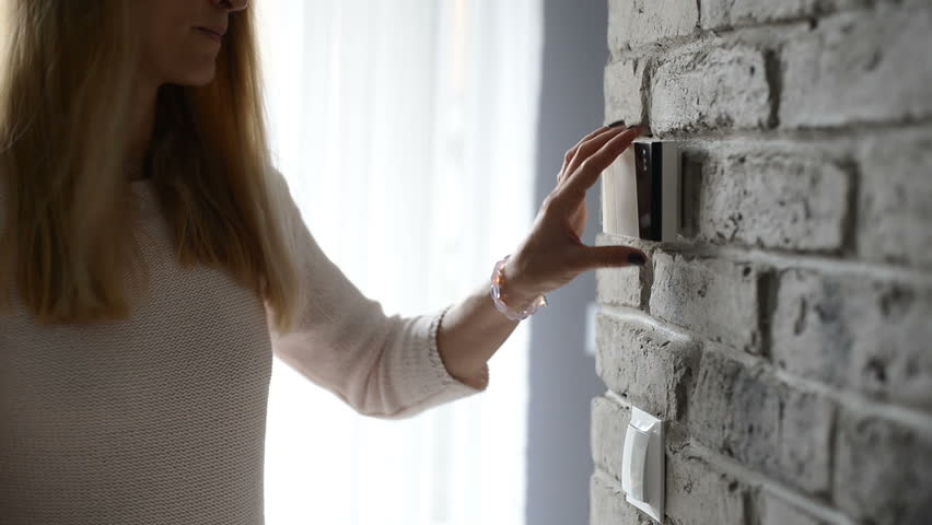 Woman entering pin on home security alarm keypad on the wall
