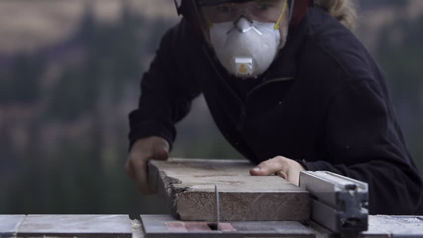 Wearing appropriate safety and protective gear (goggles, hearing protectors, dust mask) a carpenter makes a lengthwise cut in a board using a table saw.