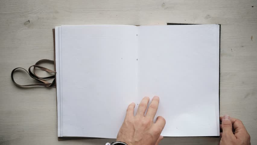 Man's hands turning over clean blank pages from recycled paper in big notebook, isolated on white wooden table , then closing it, wrapping around with leather cord and taking away