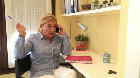 Businesswoman talking on the phone working at home