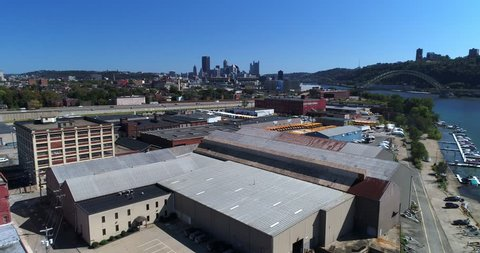 A mid-day aerial establishing shot of the Pittsburgh skyline with the warehouse business industrial park in the foreground.