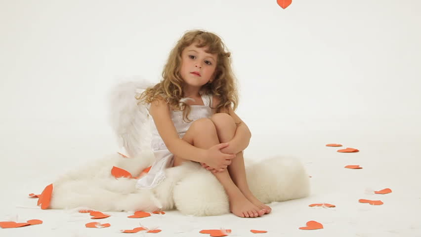 Little girl dressed as angel posing for camera.