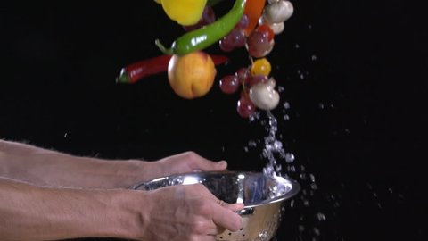 Fresh food. Super slow motion. Fruit and vegetables flying out of colander with water drops.  Multi colored shot on a black background. Man's hand  washes food. Food footage. 200 fps. 06