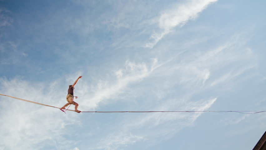 Lublin, Poland - July 2017: Slackliners in old town at Urban Highline Festival placed in old city space. Slackliner goes from left to right side of the frame. Sunny. Medium. Stabilized