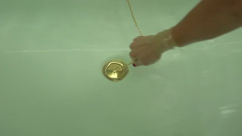 A female tanned hand pull off golden-colored chain with bath tub drain stopper from white bath filled with transparent water.