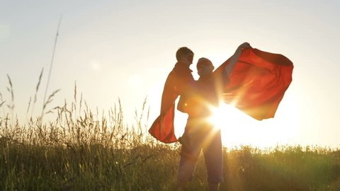 Father and son playing superhero at the sunset time. People having fun outdoors. Concept of friendly family.