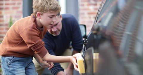 Son helping Father wash car