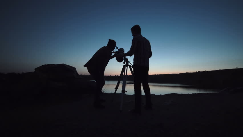Silhouettes of people looking through telescope on shore of lake in dark.