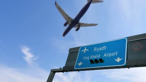 airplane flying over riyadh airport signboard