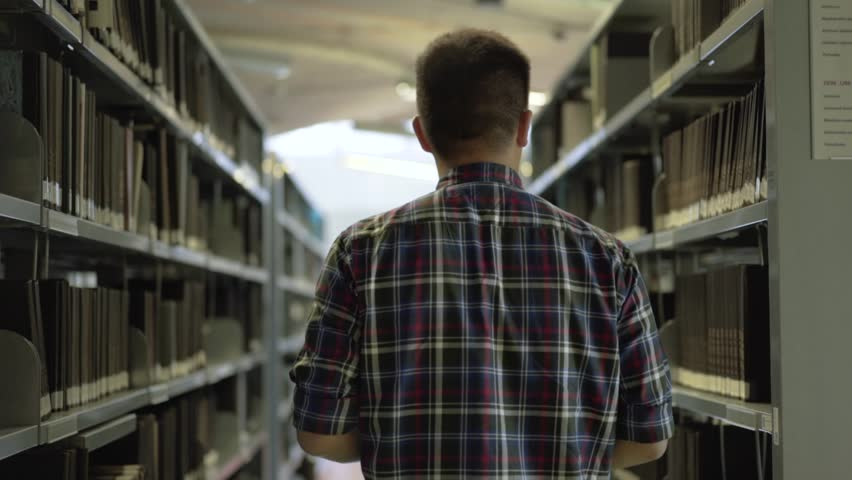 Back view shot of handsome young student walking between book shelf. Happy boy student searches for his book in library. Slow motion | Shutterstock HD Video #31365034