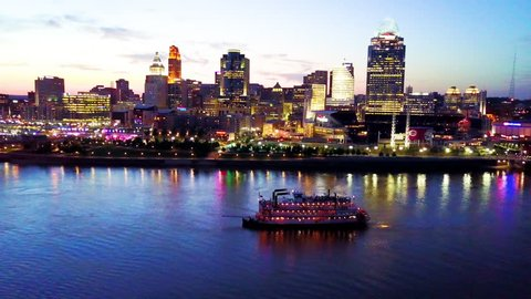 CIRCA 2010s - Cincinnati, Ohio - A beautiful evening aerial shot of Cincinnati Ohio with riverboat and bridge crossing the Ohio River foreground.