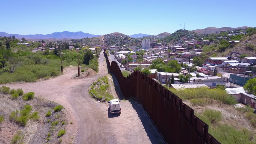 CIRCA 2010s - U.S.-Mexico border - Aerial over a border patrol vehicle standing guard near the border wall at the US Mexico border at Tecate. | Shutterstock HD Video #31374034