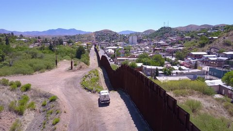 CIRCA 2010s - U.S.-Mexico border - Aerial over a border patrol vehicle standing guard near the border wall at the US Mexico border at Tecate.