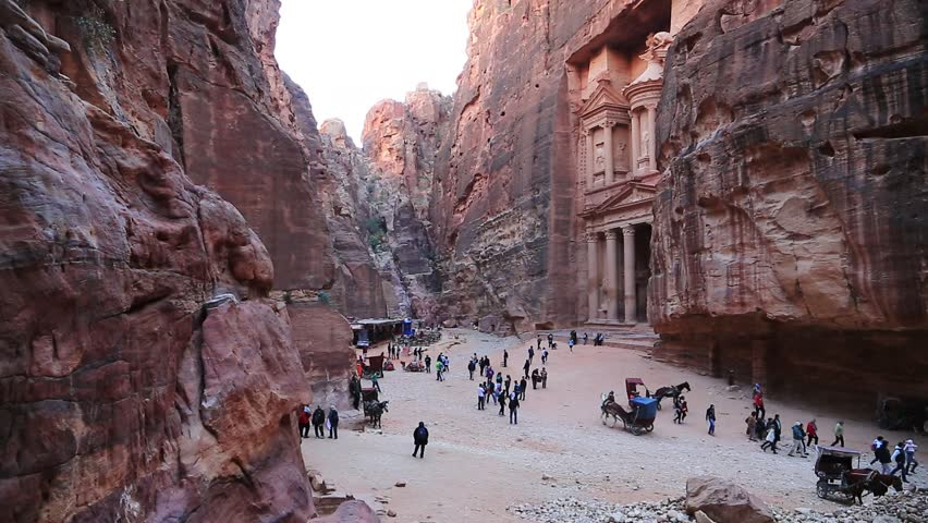 People and animals near Al Khazneh or the Treasury at ancient Petra, originally known to Nabataeans as Raqmu - historical and archaeological city in Hashemite Kingdom of Jordan