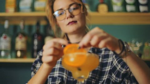 Female barmaid bartender waitress decorating preparing alcohol ice orange cocktail young lady bar interior eyeglasses friendly smile service bar give presenting drink beverage closeup front view