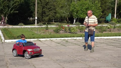 4K Young and old having joy riding a radio-controlled car