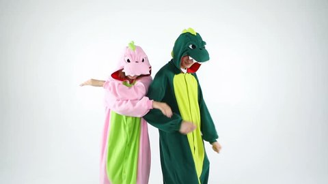 dinosaur costumes funny dancing couple. Having fun party mood people. White background video footage