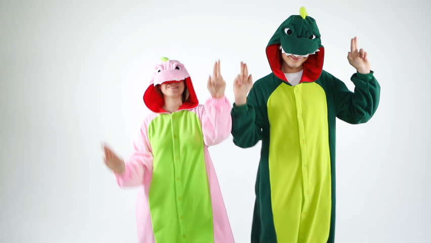 Adorable funny couple having fun. Party dinosaur costumes two young people  dancing . White background video footage