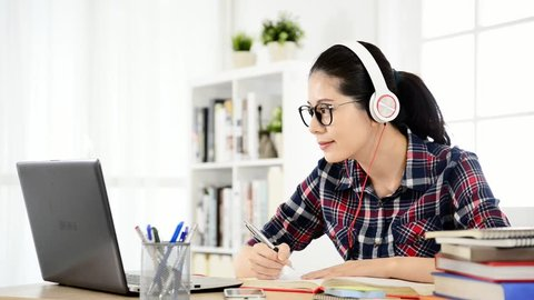 student learning online with headphones and computer laptop. mixed race asian chinese model.