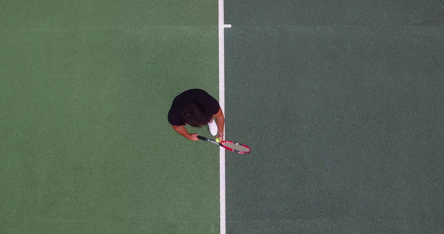 A young man playing tennis serves.