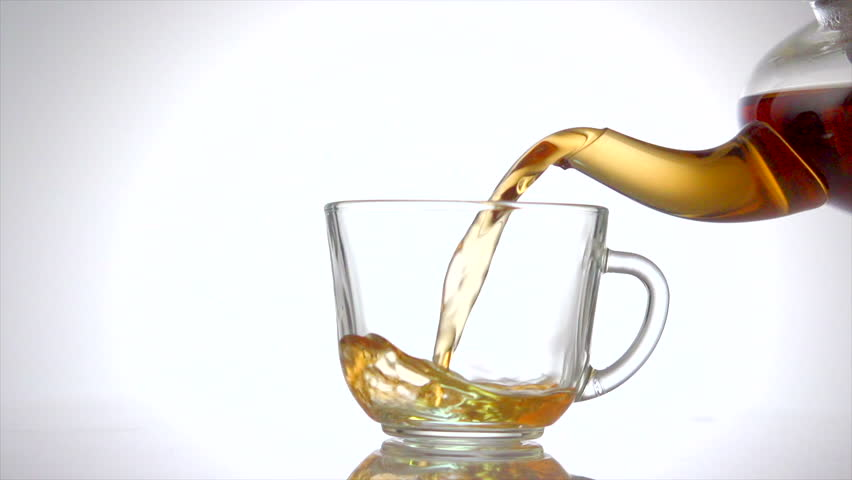 Tea pouring. Tea being poured into glass transparent tea cup. Tea time. Transparent glass teapot and teacup. Slow motion 240 fps. 4K UHD video 3840X2160